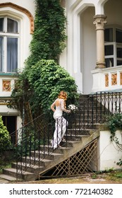 Young bride on the stone steps of a beautiful villa.