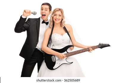 Young bride playing electric guitar and the groom signing on a microphone behind her isolated on white background