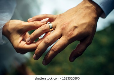 Young bride put a gold wedding ring on the groom's finger, close-up. Wedding ceremony, exchange of rings. On the hand of man wearing a wedding ring.