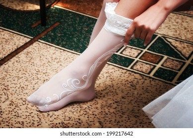 Young bride is putting on white stocking