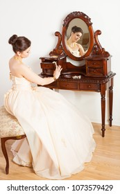 young bride wearing ball gown sitting near dressing-table with jewellery