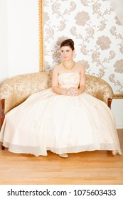 young bride wearing ball gown sitting on sofa