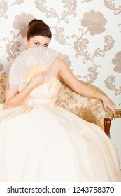 young bride wearing ball gown with fan sitting on sofa