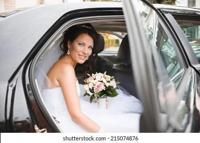 Young bride in a wedding car. Bridal bouquet.