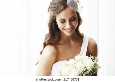 Young bride in wedding dress holding bouquet, studio shot