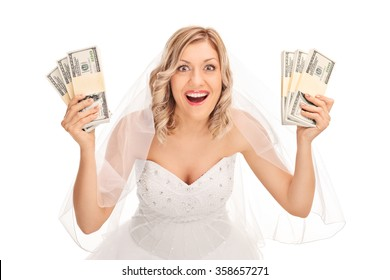 Young bride in a white wedding dress holding few stacks of money isolated on white background