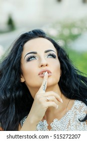 Young bride woman brunette with pretty face vogue makeup in wedding dress holding her finger with tattoo near mouth outdoor