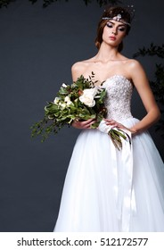 Young bride woman in wedding dress on grey background in the studio holding flowers with make up and hairstyle