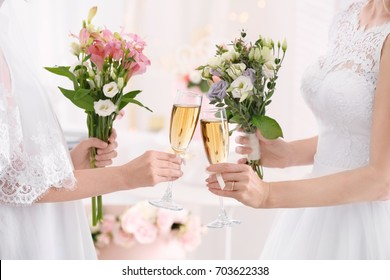 Young brides holding bouquets of beautiful flowers and glasses with champagne on lesbian wedding