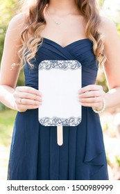 young bridesmaid wearing a navy dress and long hair holding a blank wedding ceremony program fan