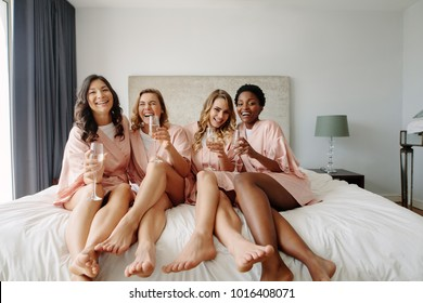 Young bridesmaids in silk robes drink champagne in hotel room. Beautiful females celebrating bachelorette party, sitting on bed and having champagne.