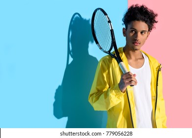 Young bright african american guy holding tennis racket and looking away on pink and blue background