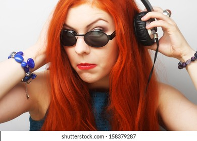 Young bright redhair woman with headphones listening music