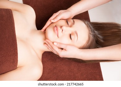 Young bright woman receiving head massage in spa center