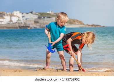 Young brother and sister having fun, digging in the sand on a beach in St Ives, Cornwall, England.