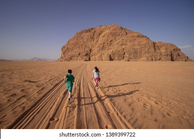 Young brother and sister are running through the Wadi Rum desert following the car tracks that leads to the huge rock mountain place of the Lawrence of Arabia in Jordan