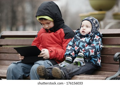 Young brothers sit together on a wooden park bench in warm winter clothing with the older child using a tablet computer