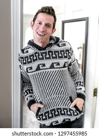 A young, brown haired, mixed ethnicity, thirty year old gentleman wearing a patterned sweater, standing and leaning in the doorway hands in sweater pockets while smiling at the camera.