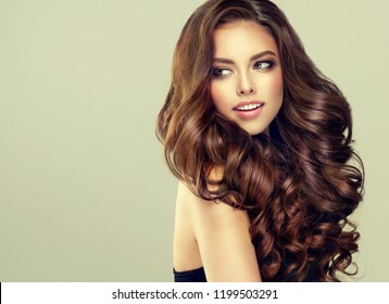 Young, brown haired woman with voluminous hair.Beautiful model with long, dense, curly hairstyle .