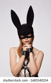 A young brown-haired lady in a white silk spaghetti-strapped shirt is wearing a black harness, leather wristbands and a black velvet bunny mask with long ears. The lady is posing on a gray backdrop.