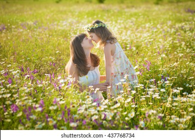 Young brunet woman with daughter sitting in a chamomile field and enjoying sunny day.Nice vacation on a chamomile field.Attractive brunet mother with daughter in chamomile glade looking on each other
