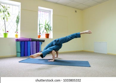 Young brunette of American origin sits on yoga mat and performs longitudinal twine. Short-haired sportswoman dressed in blue sports pants and blue t-shirt. Room light and spacious, under wall multi