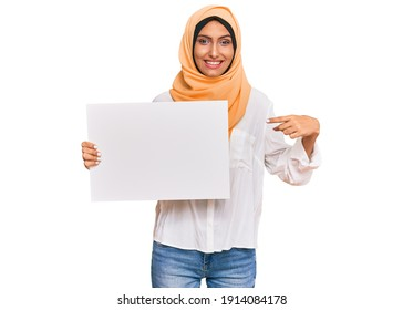 Young brunette arab woman wearing traditional islamic hijab holding banner smiling happy pointing with hand and finger