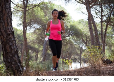 Young brunette athlete with water bottle and sports watch running through forest with hair bouncing around