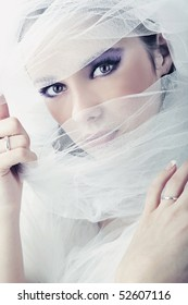 Young brunette beauty or bride, behind a white veil