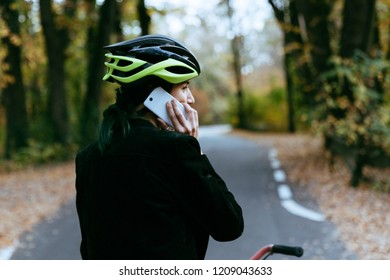 Young brunette with bike helmet talking on smartphone at sunset