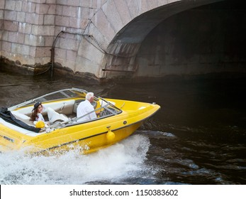 Young brunette in black hat and dress smiling rides on a speedboat. A yellow speedboat drives under the bridge.
