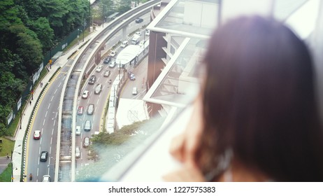 Young brunette blurred woman looking through the window on focused urban city view with buildings and roads.