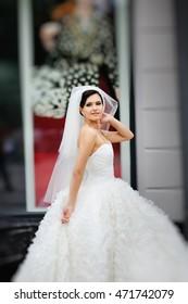 Young brunette bride wearing white dress walking street