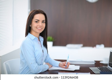 Young brunette business woman looks like a student girl working in office. Hispanic or latin american girl standing straight