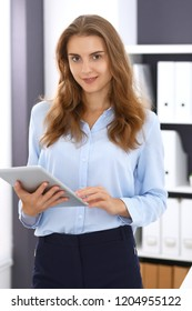 Young brunette business woman looks like a student girl at work in office. Girl standing straight with tablet pc