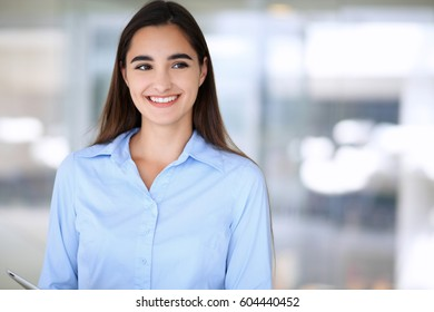 Young brunette businesswoman or student girl looking at camera.