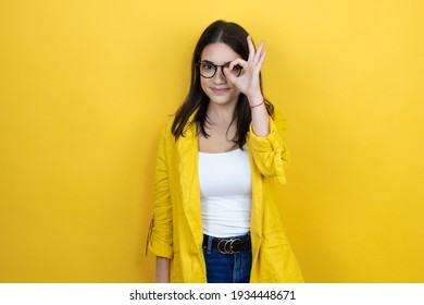 Young brunette businesswoman wearing yellow blazer over yellow background doing ok gesture shocked with smiling face, eye looking through fingers