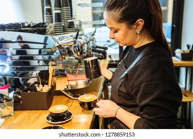 Young brunette caucasian woman barista pouring milk to make cappuccino hot drink. Small local business work in cafe. Skillful staff and real work concept.