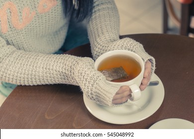 Young brunette Caucasian woman is drinking tea at a bar.