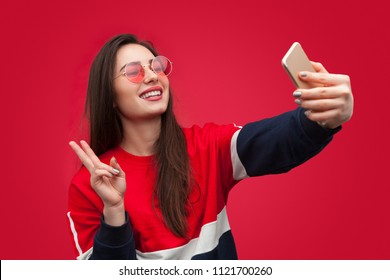 Young brunette in colorful sweatshirt and sunglasses showing two fingers and taking selfie with smartphone on red background