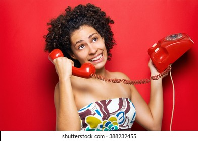 A young brunette and curly hared woman using a vintage circular dialer phone.