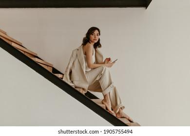 Junge brunette, lockige Frau in beigem Anzug sitzt auf hölzerner Treppe. Hübsche gegerbte Dame in Leinenhose und Jacke hält Telefon.