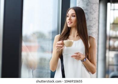 Young brunette drinking capuchino in the restorant near the window. Stylish lady drinking capuchino