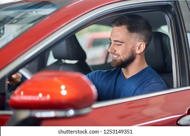 Young brunette driver sitting in red luxury car and testing it. Happy handsome man in blue sweater driving new auto. Attractive customer with beard smiling and looking at indoor design of vehicle.