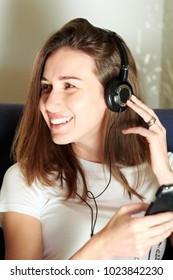 Young brunette in earphones enjoying music and using phone looking away.