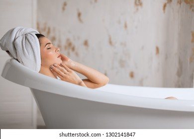 Young brunette, european woman treats herself to a comforting warm aroma bath, release tension, gets free her body of the everyday strains and stress