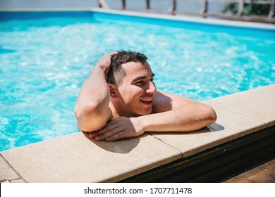 A young brunette European-looking guy peeps from the pool on a sunny day
