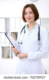 Young brunette female doctor standing with clipboard and smiling at hospital.