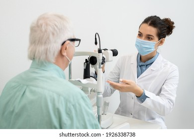Young brunette female ophthalmologist in whitecoat and protective mask going to test eyesight of senior male patient sitting in front of her
