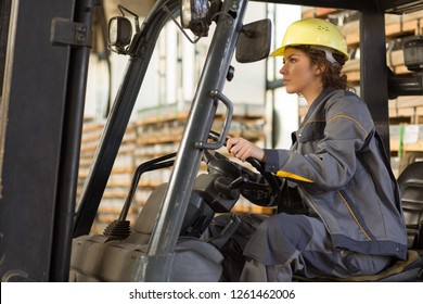 Young brunette female wearing in gray uniform and yellow helmet,  driving and making operating on forklift truck at warehouse. Woman industrial worker looking forward, working in logistic and shipment